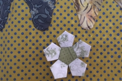 Pentagon flower using scraps of fabric from my stash with centre made from two very small pieces of treasured cloth